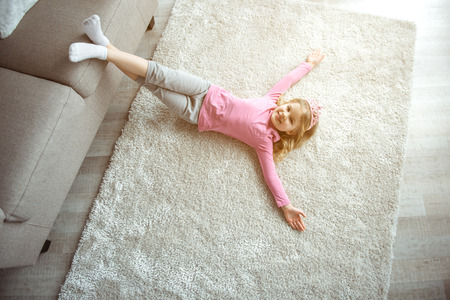 Top view of cute little princess relaxing on comfortable rug at home. She is putting feet of couch and stretching hands sideways. Child is laughing Stok Fotoğraf