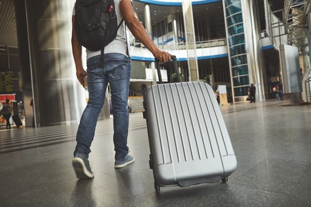 Low angle of a plastic silver luggage carried by a man who is hurrying up not to miss his flight Stock Photo