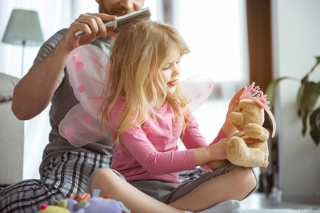 Cheerful father is making hairdo to his little loving daughter. Cute child is wearing small pink crown on her teddy bear with interest while sitting on floor Stock Photo