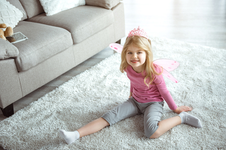 Portrait of cheerful kid playing as a princess at home. She is sitting on soft carpet while wearing pink crown and wings. Child is looking at camera and laughing