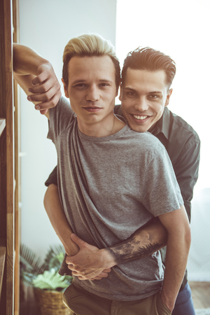 Waist up portrait of handsome guy with dyed hair leaning against wooden wall unit while his boyfriend embracing him from behind. Guys posing at home Stock Photo