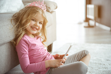 I like playing computer games. Portrait of cute kid having fun with tablet in living room. She is sitting on carpet and laughing