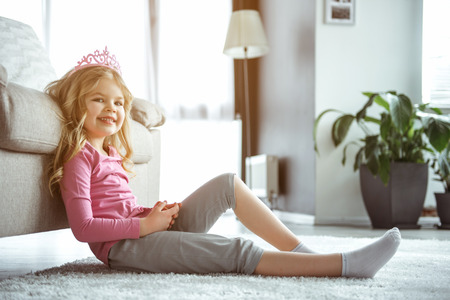 I want to be a princess. Portrait of dreamful blonde female kid is relaxing at home. She is wearing pink crown and smiling happily