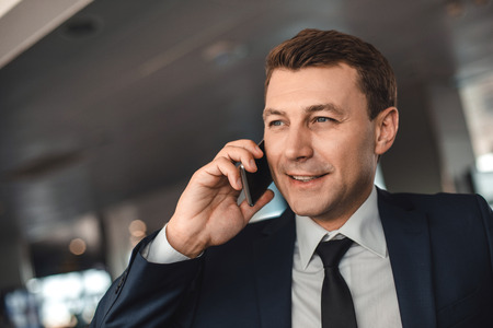 Interested businessman speaking on smartphone and looking ahead with smile Stock Photo
