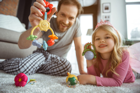 Seeing by the eyes of infant. Low angle of happy dad and small sister holding playthings in front of the toddler. They are relaxing on soft carpet and laughing Stock Photo