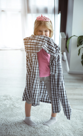 Pretty little girl is dreaming of being adult. She is wearing oversized shirt of father while standing in apartment