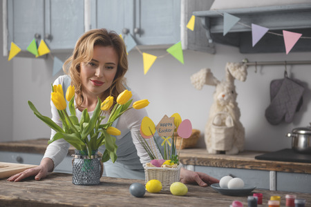 Easter preparation. Waist up portrait of calm lady standing in kitchen and beholding tulips in vase
