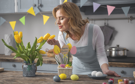 Smiling lady smelling beautiful tulips while preparing for easter dinner at home Stock Photo