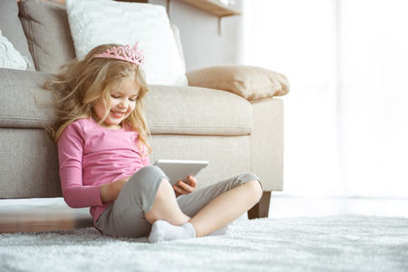 Adorable little girl is entertaining with gadget at home. She is touching screen and laughing. Child is sitting on floor near couch and wearing pink crown. Copy space Stock Photo
