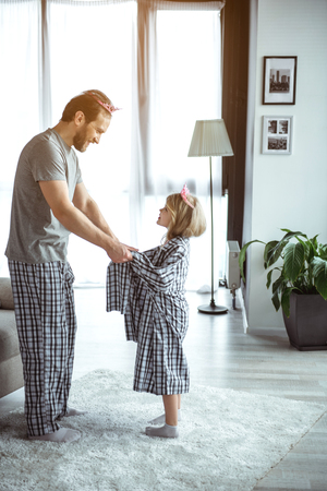 You are my heart. Happy father is holding hands with his little daughter. They are standing in living room and smiling. Family is wearing one pajamas on both and pink crowns Stock Photo
