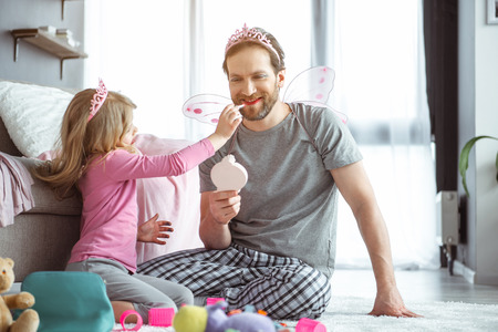 You are so pretty. Cheerful girl is applying lipstick on her father lips. Man is looking at the mirror with joy and laughing Stock Photo