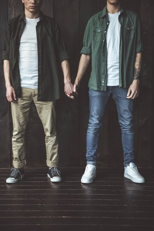 Very special bond. Cropped portrait of two young guys holding hands while standing on wooden background Stock Photo
