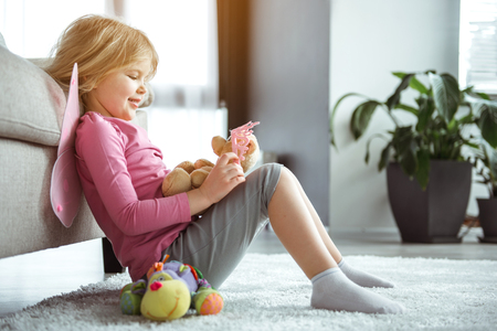Side view of excited little blonde girl is playing with teddy bear and crown. She is sitting on carpet while leaning back on sofa. Child is laughing