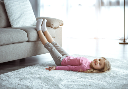 Relaxing at home. Carefree little girl is lying on floor on soft carpet while leaning legs on sofa. She is looking at camera and smiling 写真素材