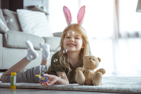 Look how I can. Portrait of happy little girl is blowing soap bubbles at home. She is lying on rug in apartment and holding teddy bear. Kid is looking at camera and smiling with proud Imagens