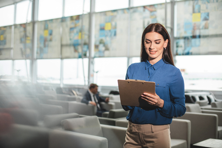 Waist up portrait of concentrated lady holding folder and looking at it with interest. She standing in cafe. Copy space on left side