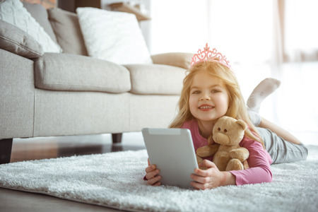 Little user. Portrait of joyful child using tablet with gladness. She is looking at camera with joy and laughing. Princess is relaxing on flooring at home