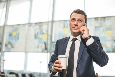 Waist up portrait of businessman holding coffee and speaking on smartphone. Copy space on left side