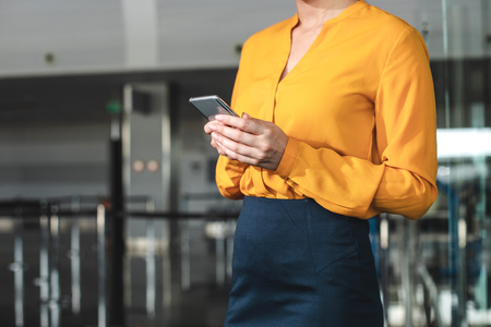 Close up of silver smartphone held by woman in yellow blouse. Copy space on left side Stock Photo