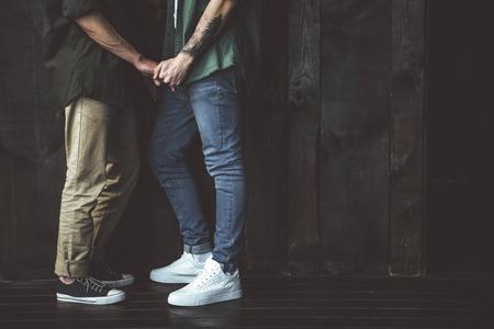 Doux amour. Portrait de vue latérale recadrée de deux homme aimant debout contre le mur en bois Banque d'images