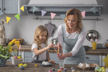 Waist up portrait of smiling mom and child painting easter eggs in the kitchen Фото со стока - 109936532