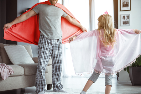 Lets fly together. Carefree man and girl are having fun in apartment. They are wearing clothes as if wings and laughing