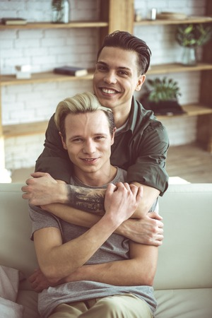 Closer to you. Toned waist up portrait of blond young man sitting on couch while his boyfriend embracing him from behind. They looking at camera with happy smiles Фото со стока - 109936544