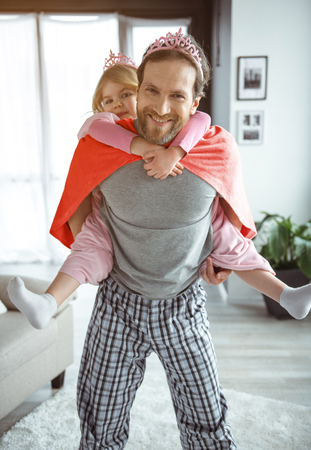 Full length portrait of joyful daddy is holding little girl on back and laughing. He is looking forward with excitement. They are wearing toy crowns
