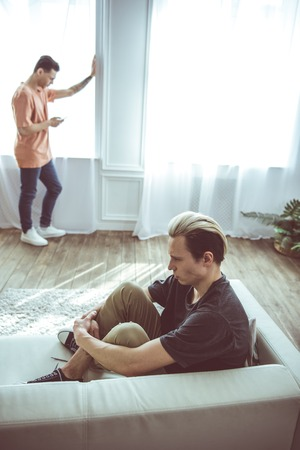 Ignoring each other. Toned portrait of unhappy guy with dyed hair sitting on couch while his boyfriend standing near window and using smartphone
