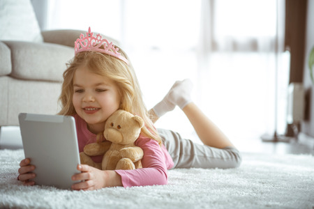 Portrait of happy little girl is watching interesting cartoon with excitement. She is holding tablet while lying on soft rug. Cute princess is smiling