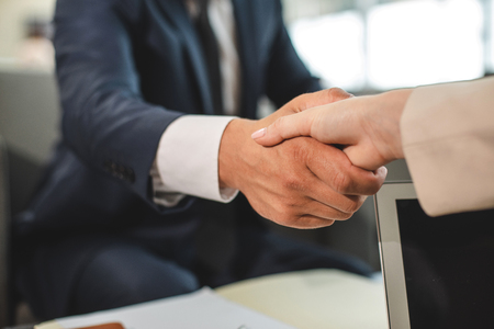 Close up of handshake of man and woman being business partners. Documents on blurred background Stock Photo