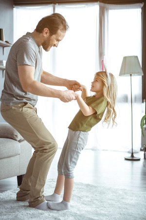 Cute little girl is dancing with her daddy while standing on his feet. She is laughing with excitement. Having fun at home together concept Stock Photo