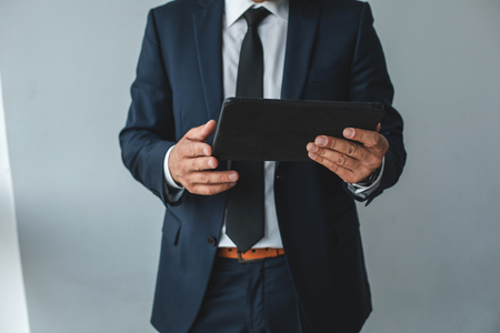 Businessman wearing black suit and holding tablet. Close up of electronic device
