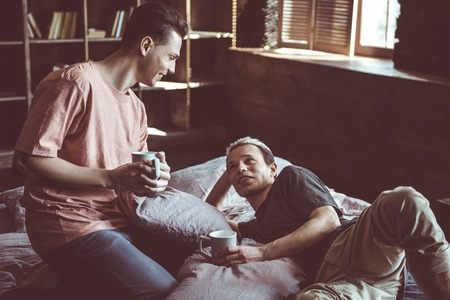 Perfect morning with you. Toned portrait of two handsome guys resting in bed and holding cups of hot drink. They looking at other and smiling Foto de archivo - 110476486