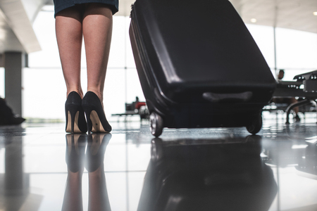 Close up of female legs wearing high heel shoes and black suitcase on wheel