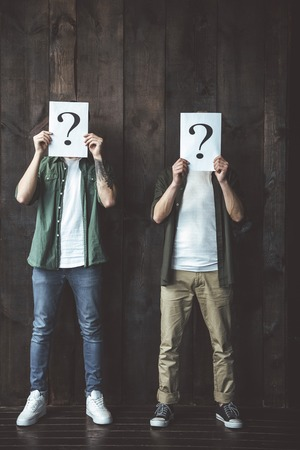 Full length portrait of two young men hiding behind posters with question mark. They standing on wooden background