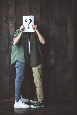 Full length side view portrait of two young men hiding behind card with question mark. They standing on wooden background