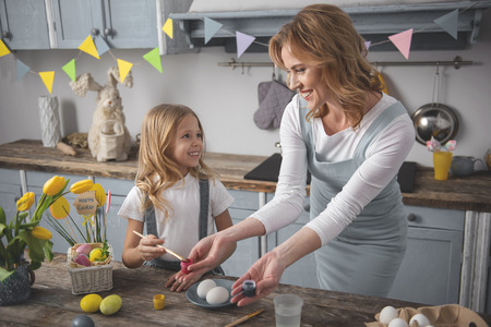 I help you. Smiling mom and daughter preparing for easter holiday while standing in the cuisine