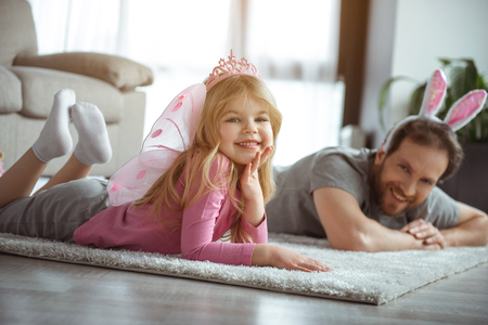 I am fairy. Portrait of charming little girl is lying on soft carpet at home. She is looking at camera and smiling while wearing crown and wings. Her father is relaxing on flooring next to her Banco de Imagens