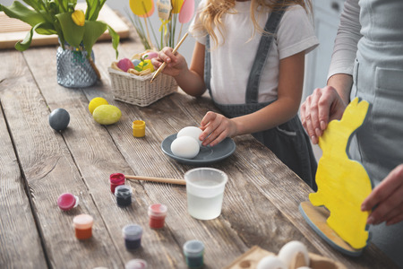 Close up of mom and kid hands painting easter decorations on wooden table together Imagens
