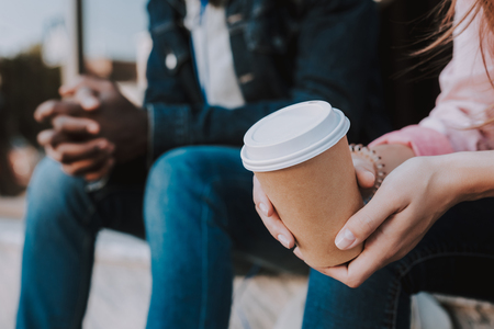Close up of a cup with tasty coffee in female hands who is sitting with her Afro American friend