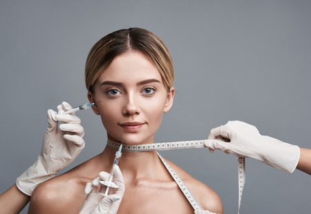 Pretty young lady having measuring tape on her neck and slightly smiling while getting necessary injections into her face