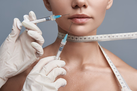 Young lady keeping calm while having measuring tape on her neck and getting injection in the lips
