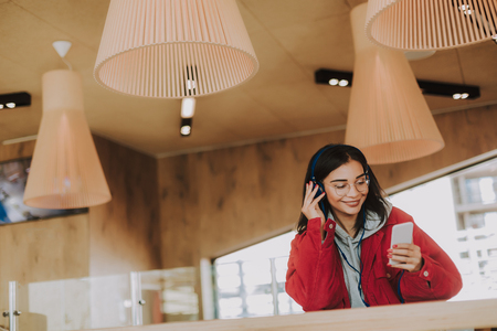 Waist up of a pleasant delighted young woman standing in the cafe while listening to music Imagens