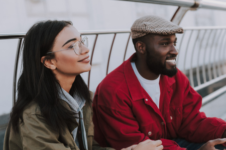 Delighted nice young woman sitting in the city with his male friend while being involved in thoughts