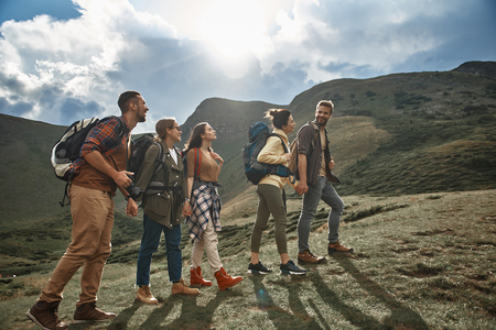Walking. Cheerful active friends wearing comfortable clothes and carrying backpacks while enjoying their mountain journey