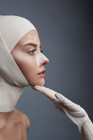 Chin up. Young serious lady looking at the doctor while being examined with bandages on her head