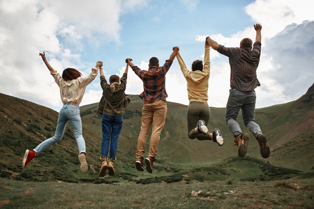 Salto in alto. Espressivo giovane gruppo di amici che si sentono eccitati e saltano mentre si trovano in cima alla collina