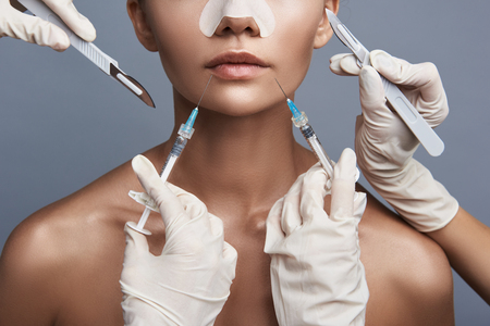 Young woman standing against the grey background while several beauticians holding syringes and scalpels near her face