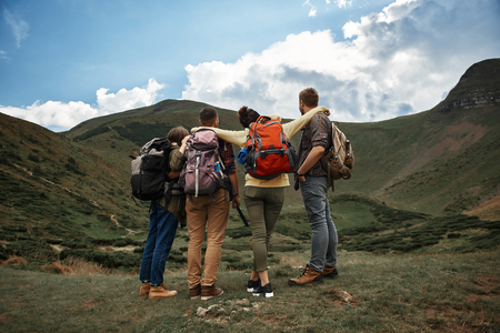 Real friendship. Active enthusiastic travelers putting hands on the shoulders of each other and looking at the breathtaking view Stock Photo